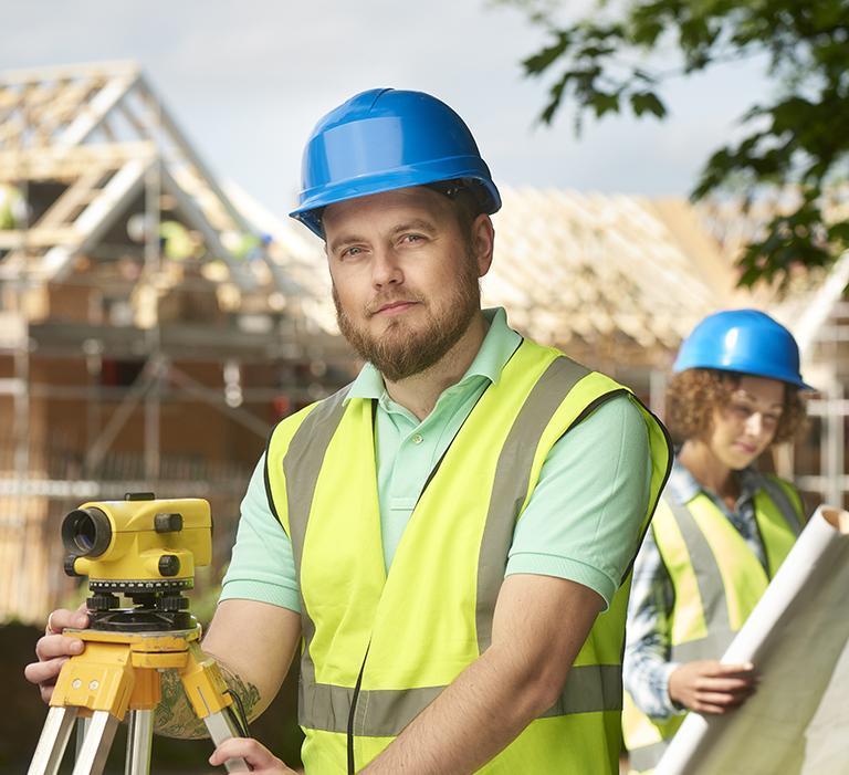 mężczyzna stoi przy teodolicie wtle kobieta zplanami idomy wtrakcie budowy